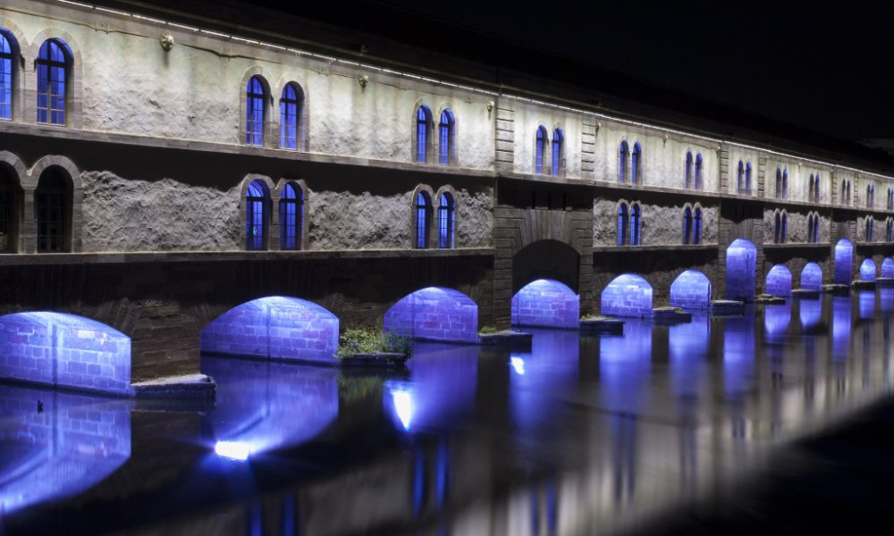 A fortified bridge with decorative blue lights under the arches
