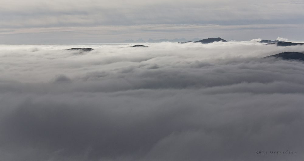 A sea of clouds with peaks of the Vosges mountains as islands and Alps in the background