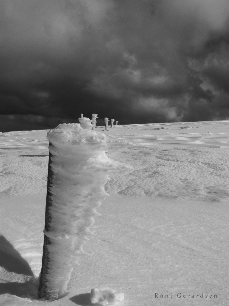 A line of iced stakes attop a snowy mountain