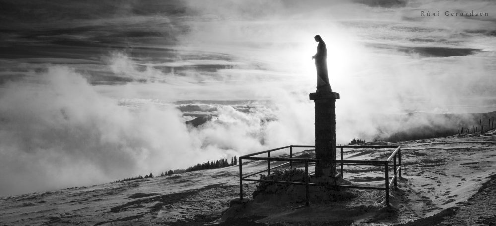 A statue of Virgin Mary sitting attop a mountain and watching a sea of clouds