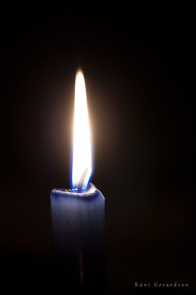 Close up on the flame of a candle in the dark