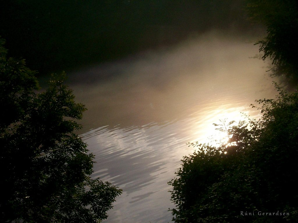A lake with the sun reflecting through the mist